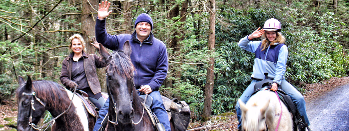 The owners of Wildfire Ranch riding a trail.